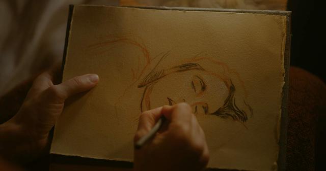 Mãos segurando papel e lápis e desenhando figura de mulher deitada de lado, dormindo