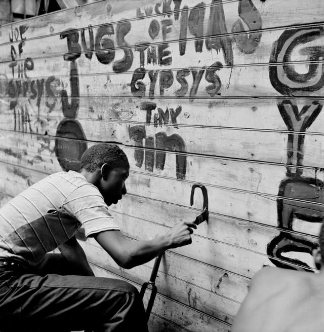 Membro de gangue grafita parede no Harlem, em Nova York, em 1948. Foto integra a primeira história proposta à 'Life' por Parks