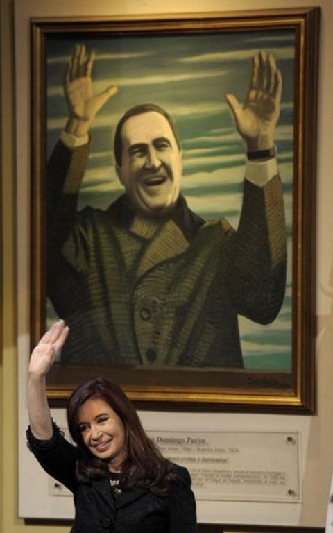 Cristina Kirchner sorri e acena dentro de um sala. Atrás dela, uma pintura na parede que representa Juan Domingo Perón com os dois braços erguidos.
