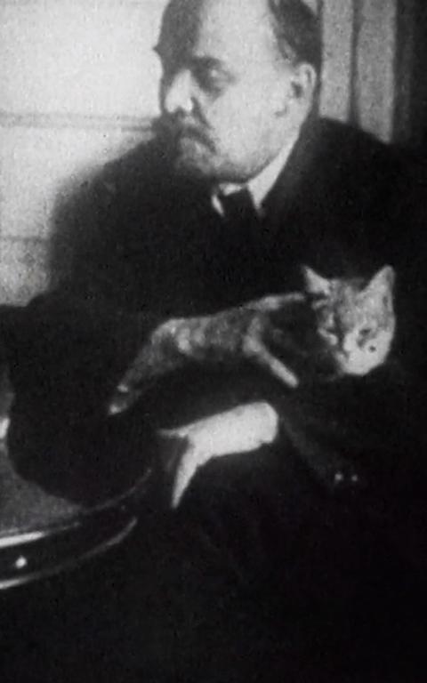 Em preto e branco, cena meio embaçada e com ruídos da película tem Lênin no centro do quadro sentado fazendo carinho no gato