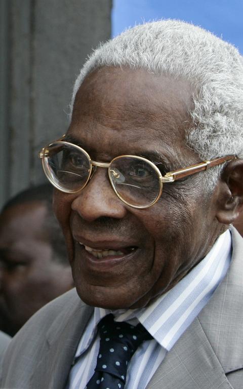 Homem idoso negro, sorrindo, de óculos de aro redondo dourado, camisa e gravata