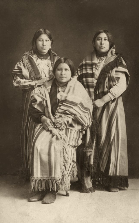 All three pose for the camera. In a sitting, and standing