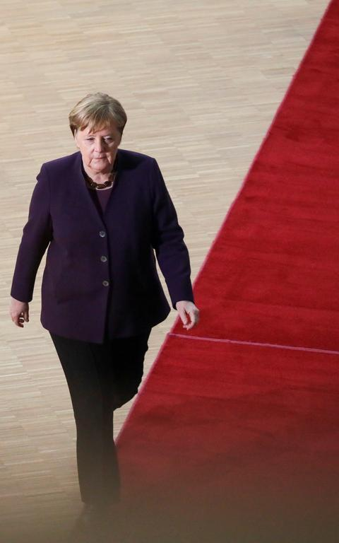 Merkel, toda vestida de roxa, caminha sobre tapete vermelho