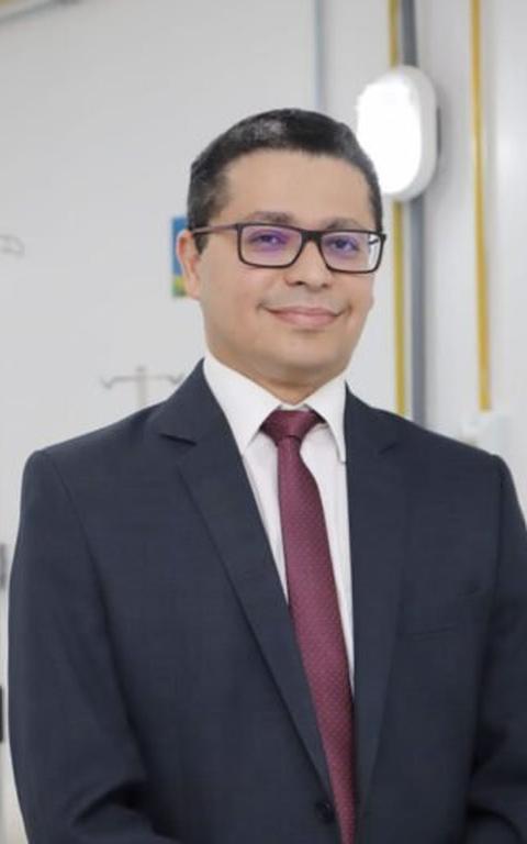 Homem branco de terno e gravata roxa sorri para a câmera