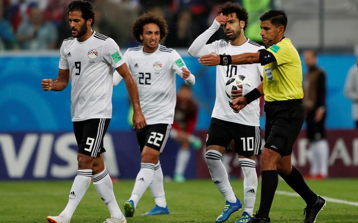 Árbitro paraguaio Enrique Cáceres sinaliza marcação de pênalti no jogo entre Rússia e Egito, após consulta ao árbitro de vídeo