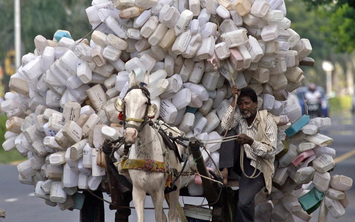 Homem transporta embalagens de plástico para depósito de lixo em Panchkula, ao norte da Índia, em 2011