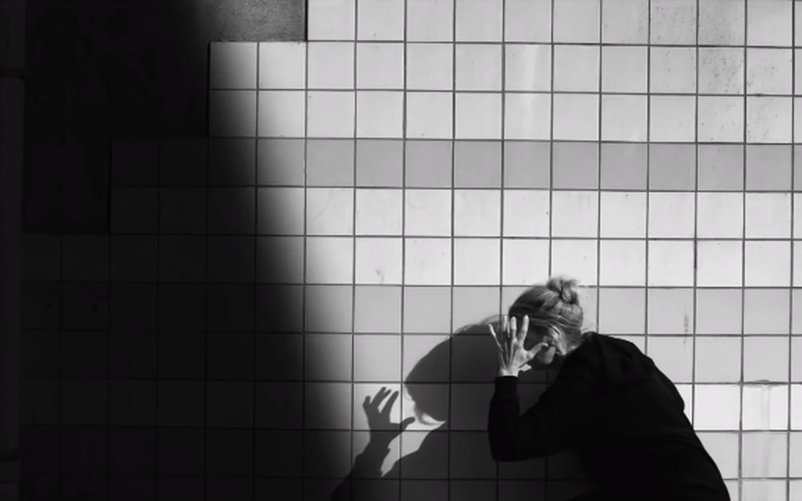 Mulher agachada, com a mão sobre o rosto e feição de sofrimento. Atrás, um muro. Em frente a ela, uma sombra se aproxima.