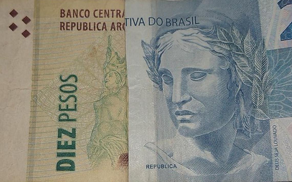 Cédula dobrada de 10 pesos argentinos, ao lado de uma nota dobrada de 2 reais. As duas metades formam como se fosse uma cédula só.