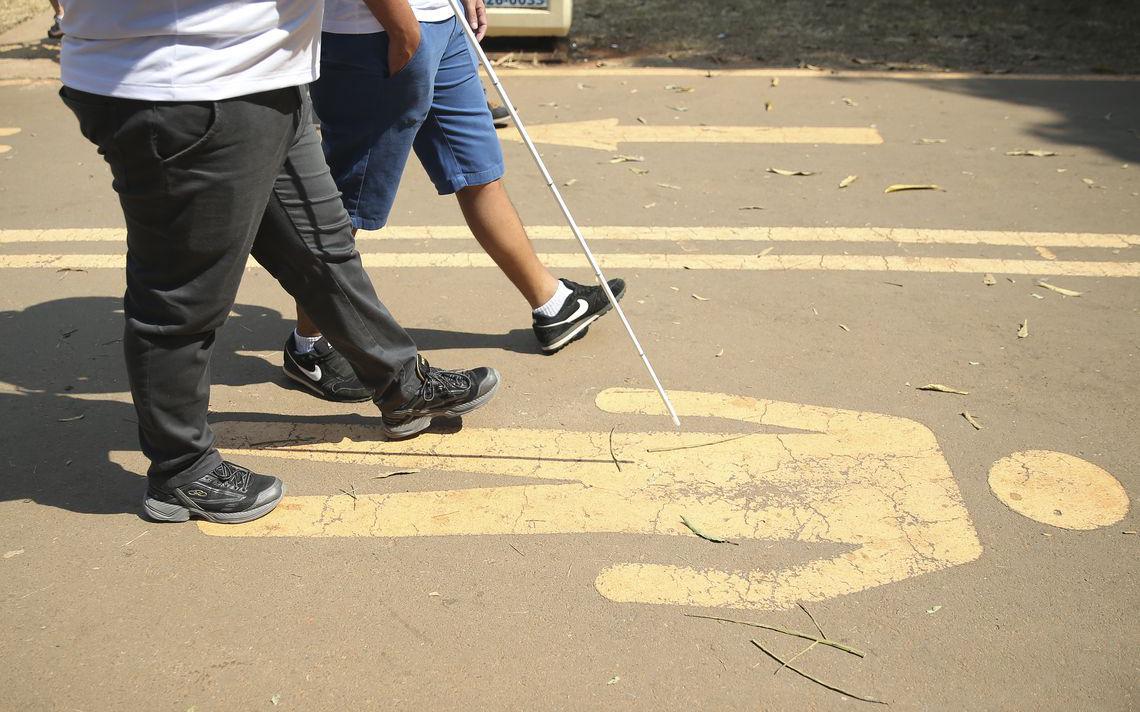 Deficiente visual caminha na rua com bastão