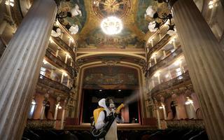 Homem com roupa branca de proteção, máscara e um pulverizador amarelo que jorra desinfetante dentro de um grande teatro