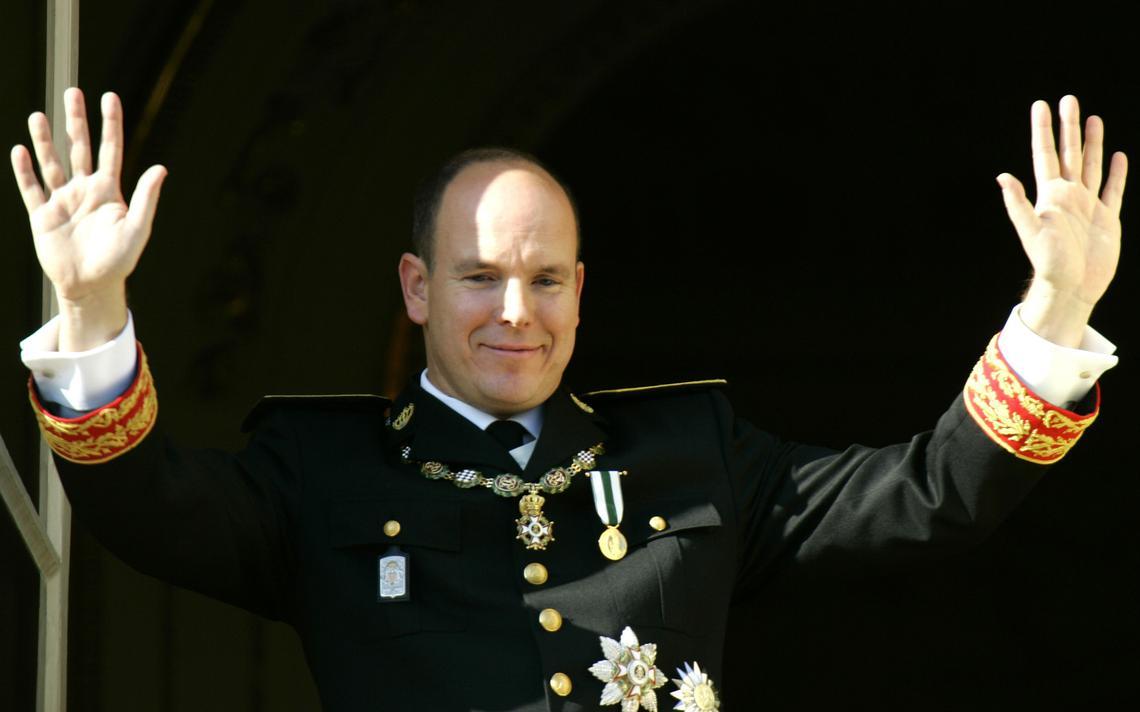 Com vestes formais e medalhas, Albert 2º acena com os dois braços levantados e as mãos abertas, na varanda do palácio.