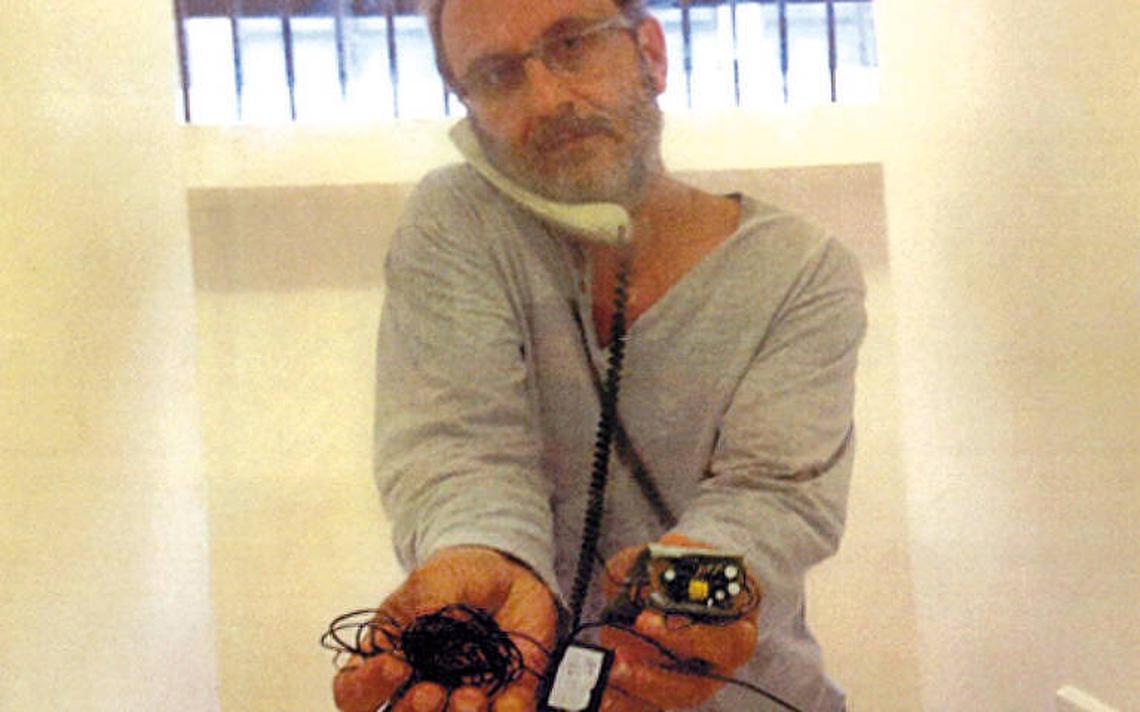 Com telefone encostado entre o ombro direito e o ouvido direito, Youssef está dentro de uma cela e posa para foto mostrando fios e aparelhos.