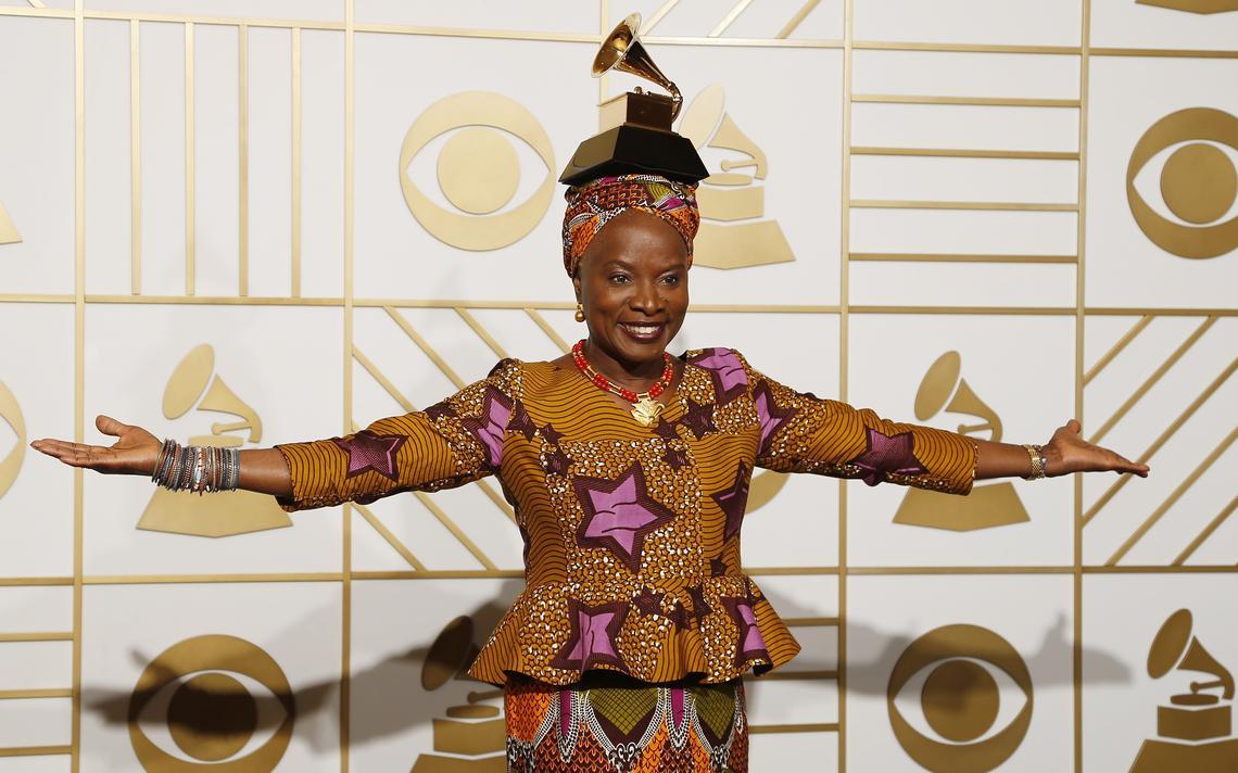 Cantora está com os braços abertos, com vestes coloridas e equilibra uma estatueta do Grammy na cabeça.