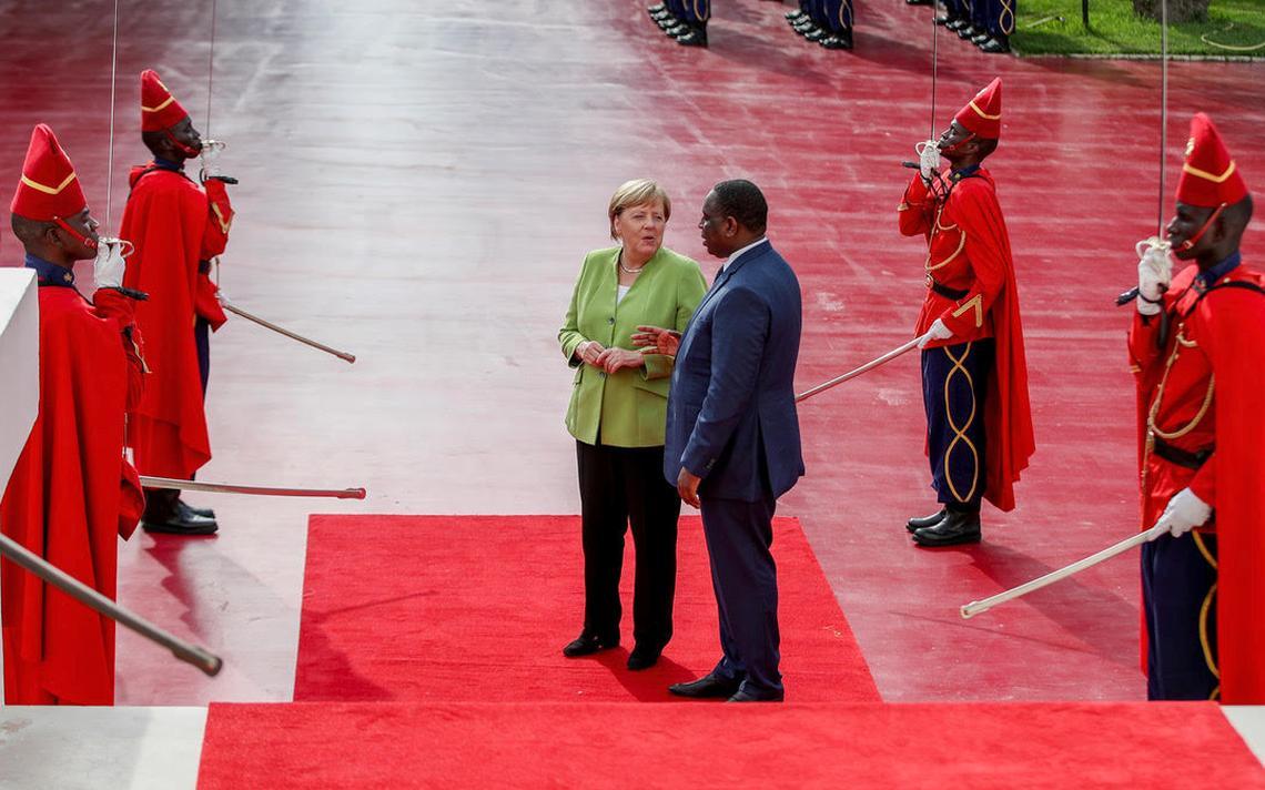 Merkel e Sall conversam em tapete vermelho. Em volta, quatro guardas em pé, usando vestes e chapéu vermelhos e segurando um sabre.