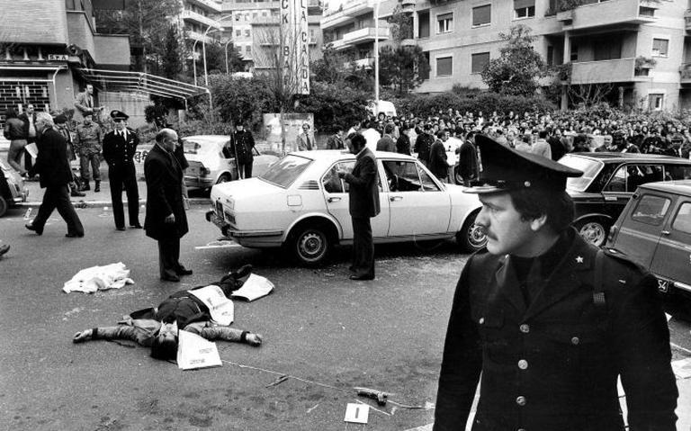 Homem morto no asfalto. Policiais e carros ao redor. Dezenas de pessoas observam a cena.