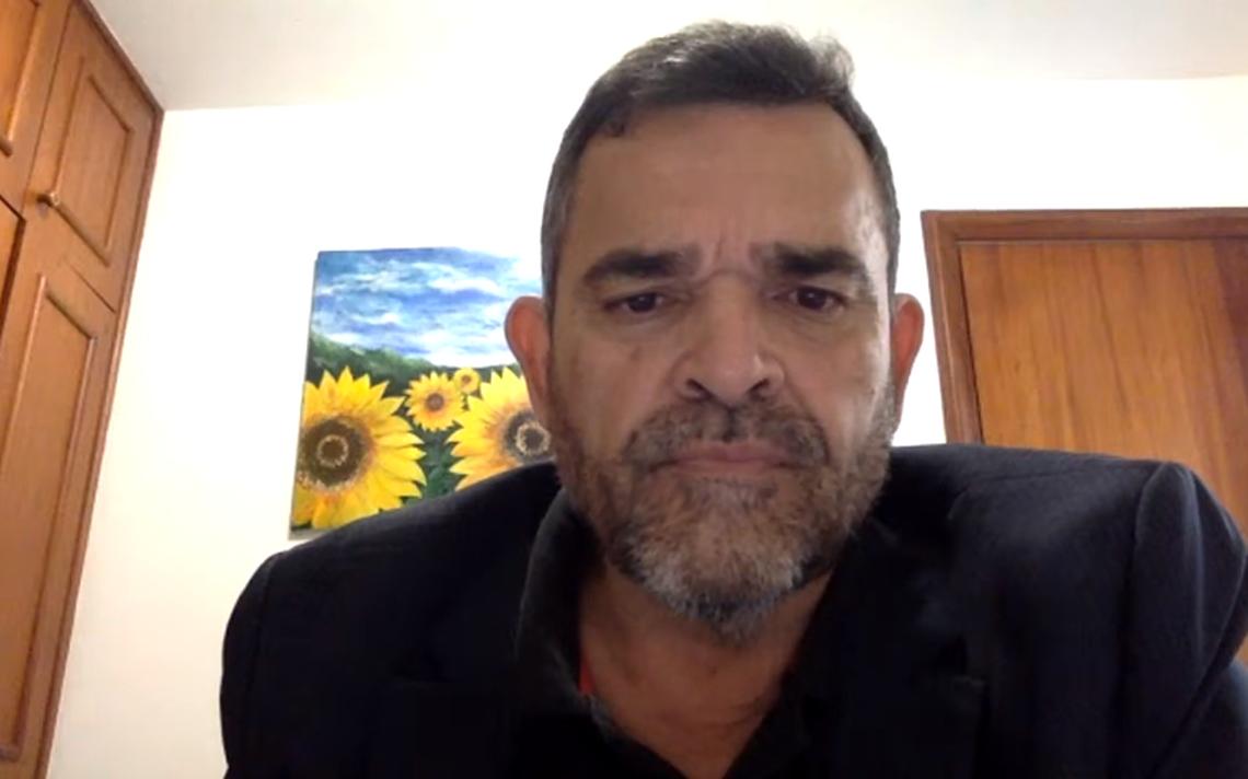 O coronel Antônio Carlos Alves Correia está sentado e fala para a câmera. Ele está dentro de um quarto. Atrás, um armário embutido, uma porta e um quadro na parede.