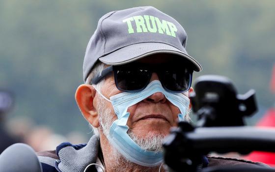 Homem com boné de Trump e máscara rasgada marcha contra medidas sanitárias adotadas na Holanda durante a pandemia da covid-19