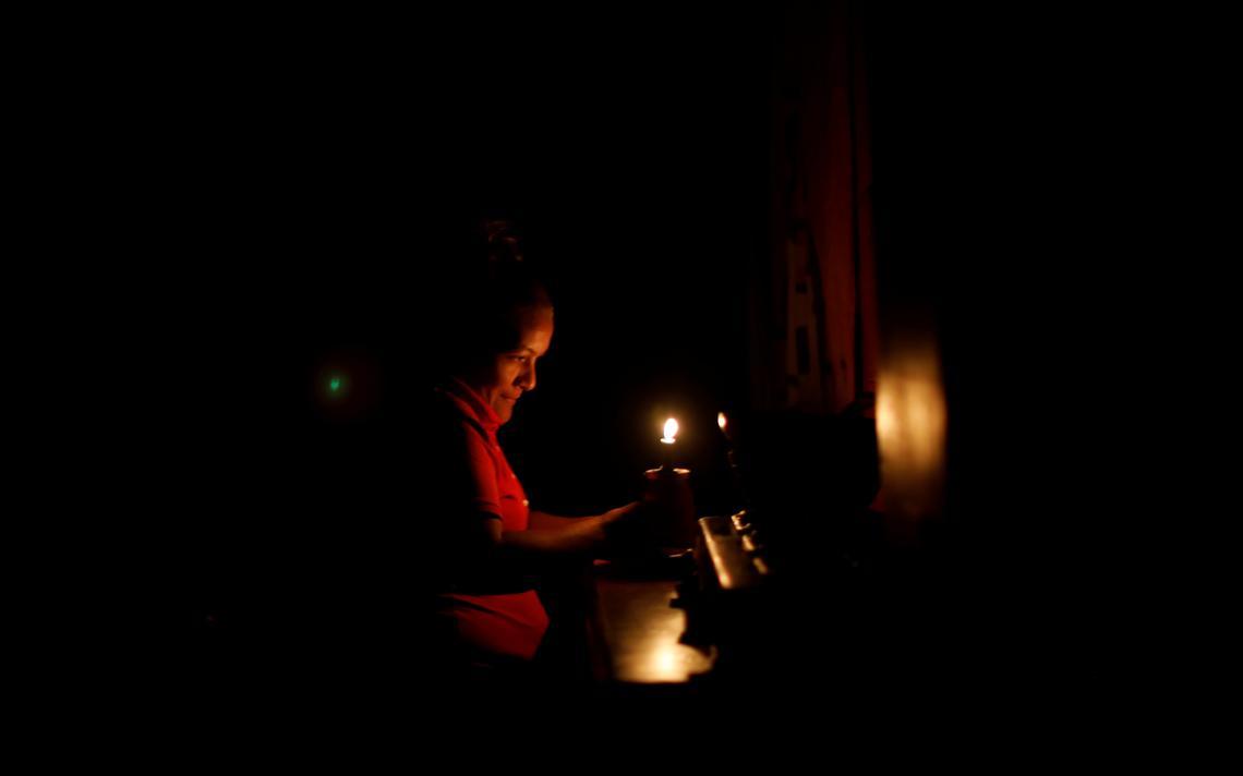 No escuro, mulher acende vela.
