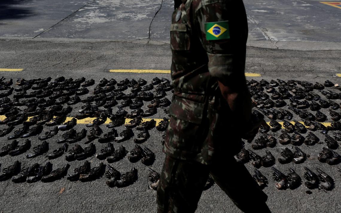 Dezenas de revólveres enfileirados e no chão, à espera da destruição, por serem ilegais. Militar fardado do Exército caminha ao lado das armas.