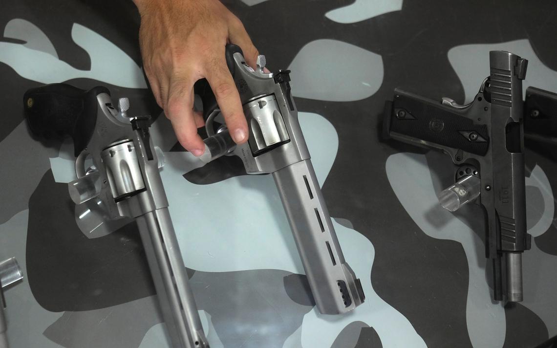 Três pistolas apoiadas lado a lado. A mão de uma pessoa segura uma das armas.