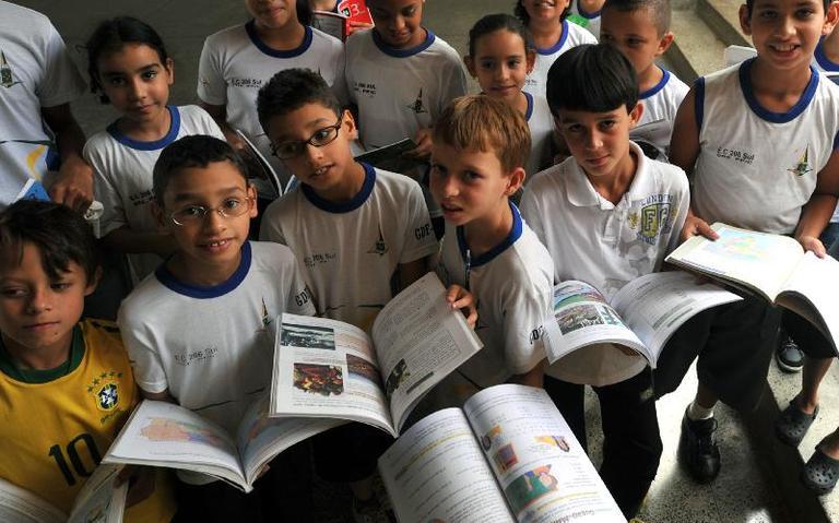Alunos de colégio de Brasília mostram livros didáticos adquiridos pelo governo, em 2011