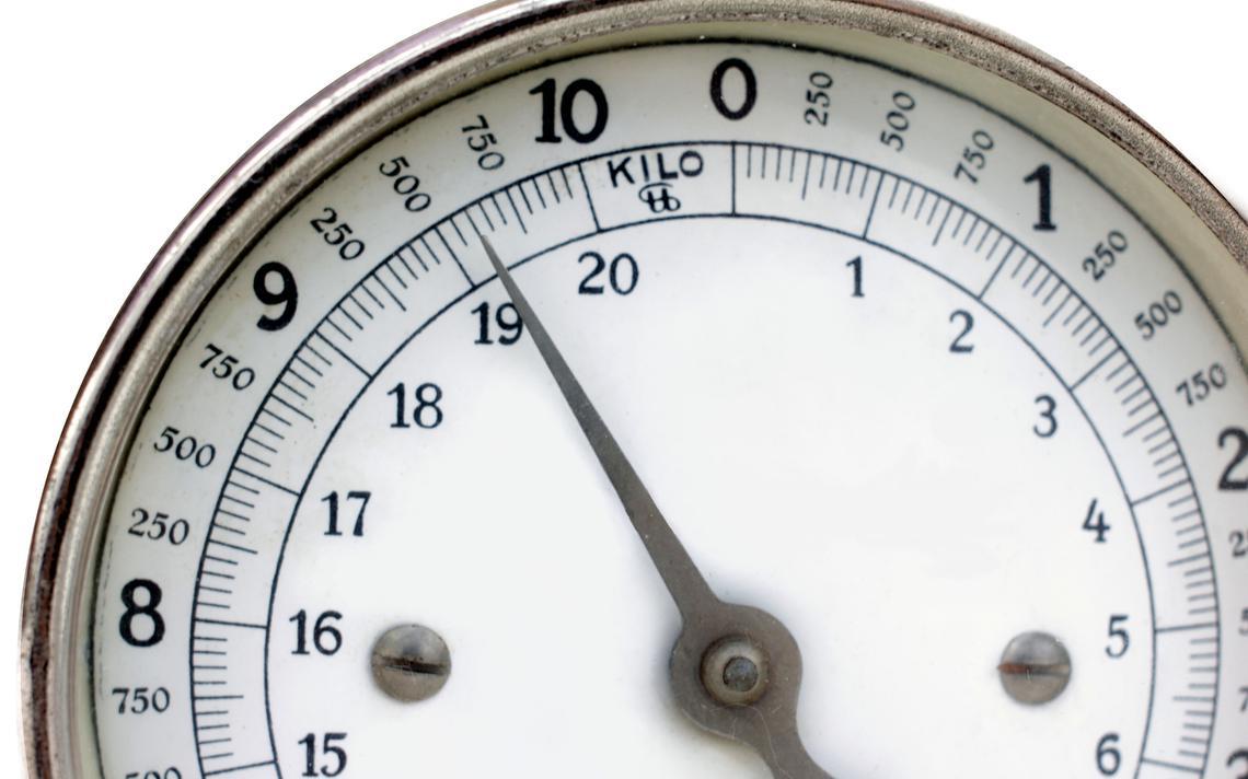 Visor de uma balança analógica, com ponteiro apontado para, aproximadamente, 9 quilos e meio.