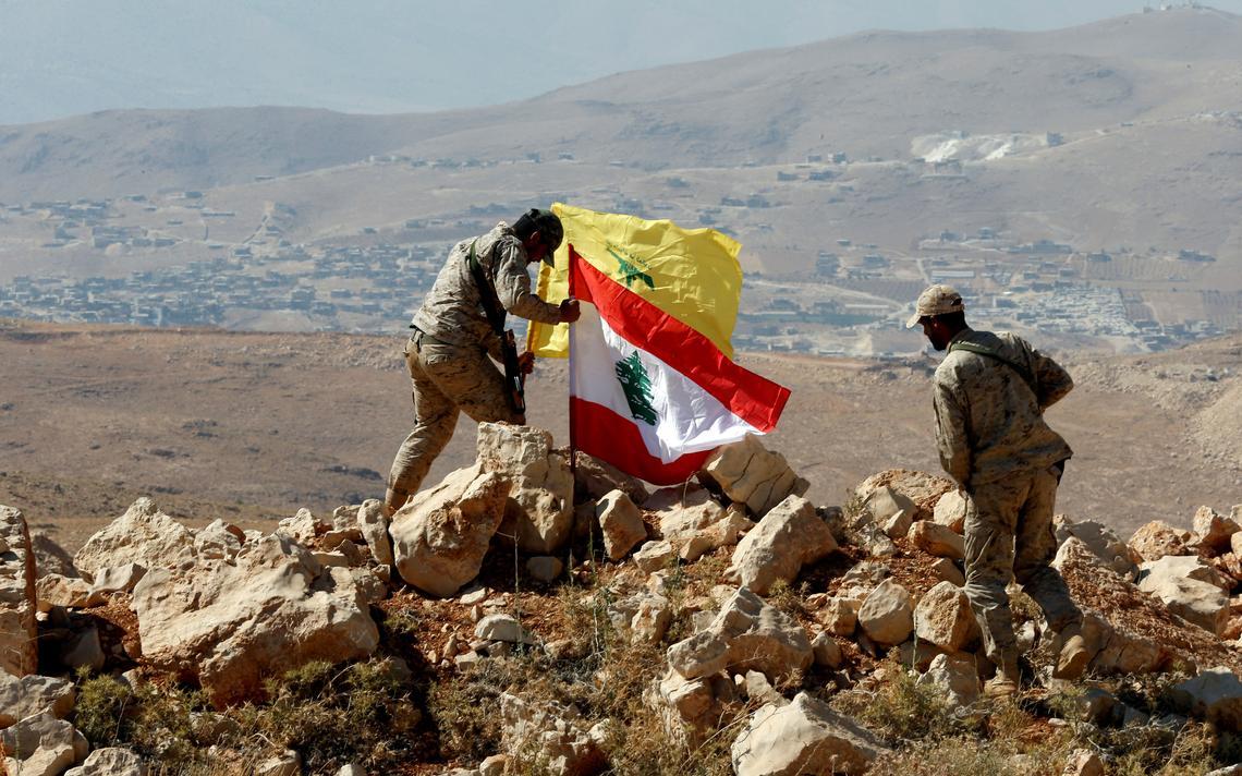 Dois soldados armados em cima de um monte pedregoso. Um deles maneja as duas bandeiras.