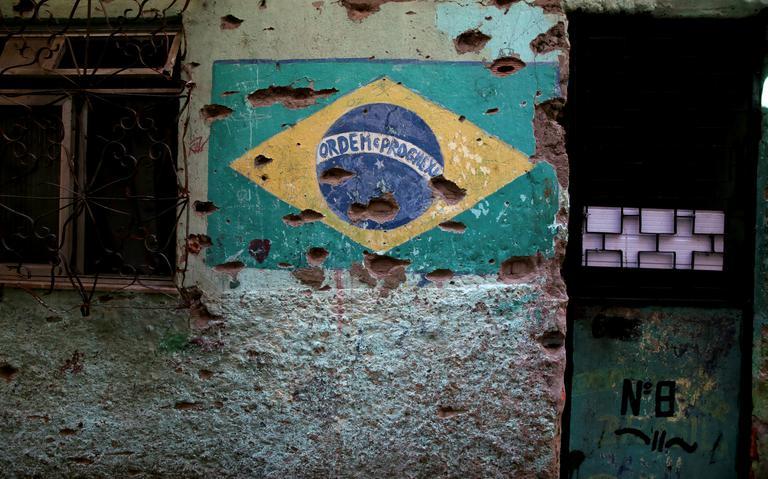 Bandeira pintada na parede cravejada de balas, na comunidade do Jacarezinho, no Rio, em 2018