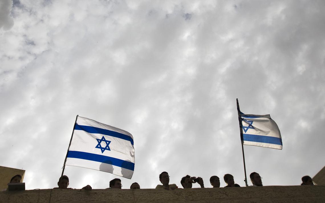 Pessoas observam a rua em parapeito de assentamento. Duas bandeiras de Israel estão hasteadas.