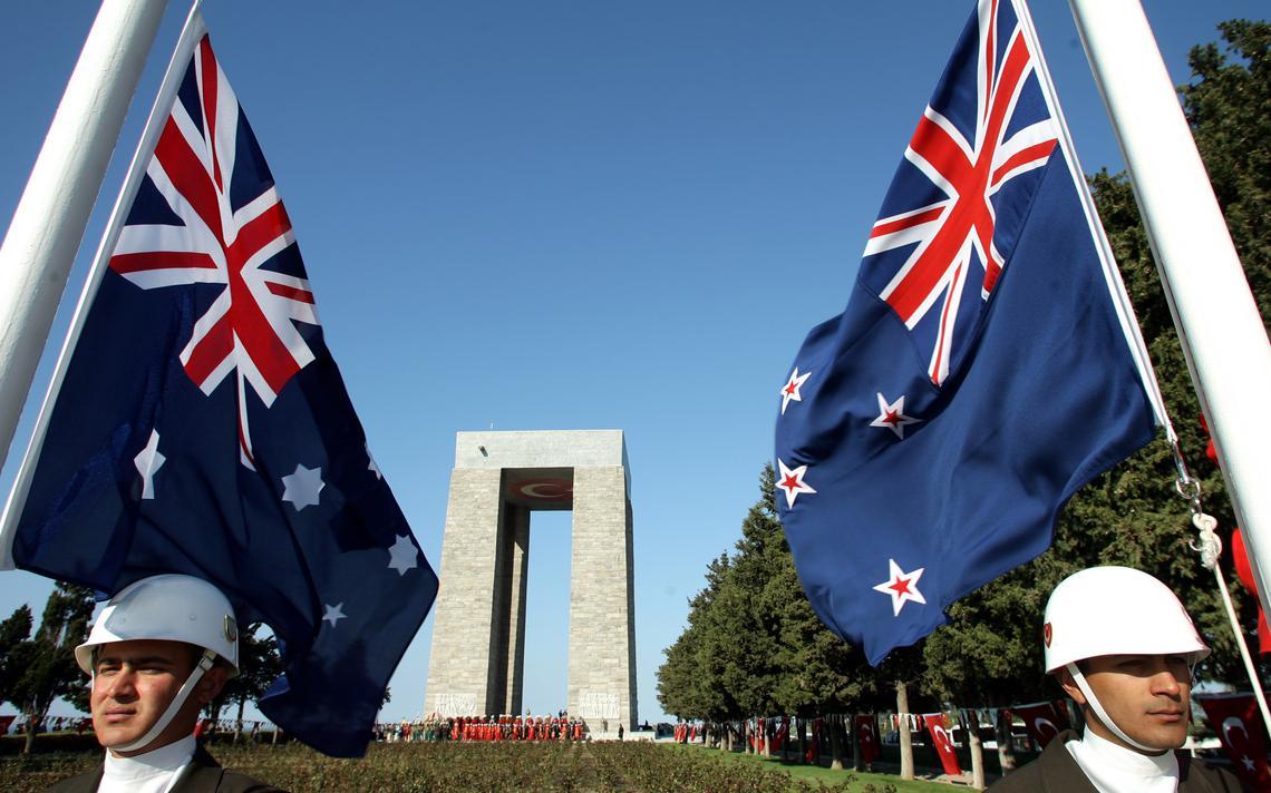 Duas bandeiras hasteadas, com um soldado a postos ao lado de cada bandeira.