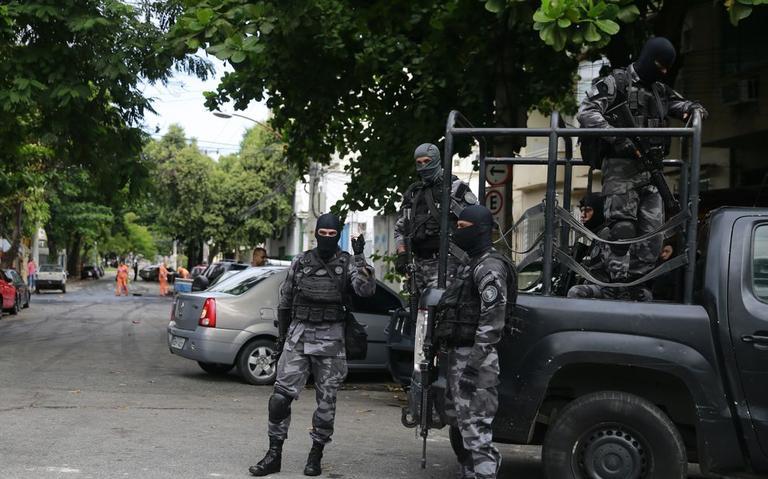 Seis policiais, fortemente armados e encapuzados. Uma viatura do batalhão de choque.