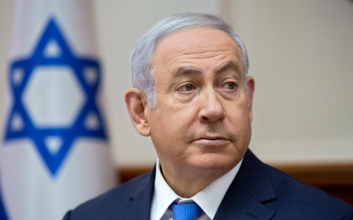 Sentado, Netanyahu olha para o lado. Atrás, a bandeira de Israel, com a Estrela de Davi.