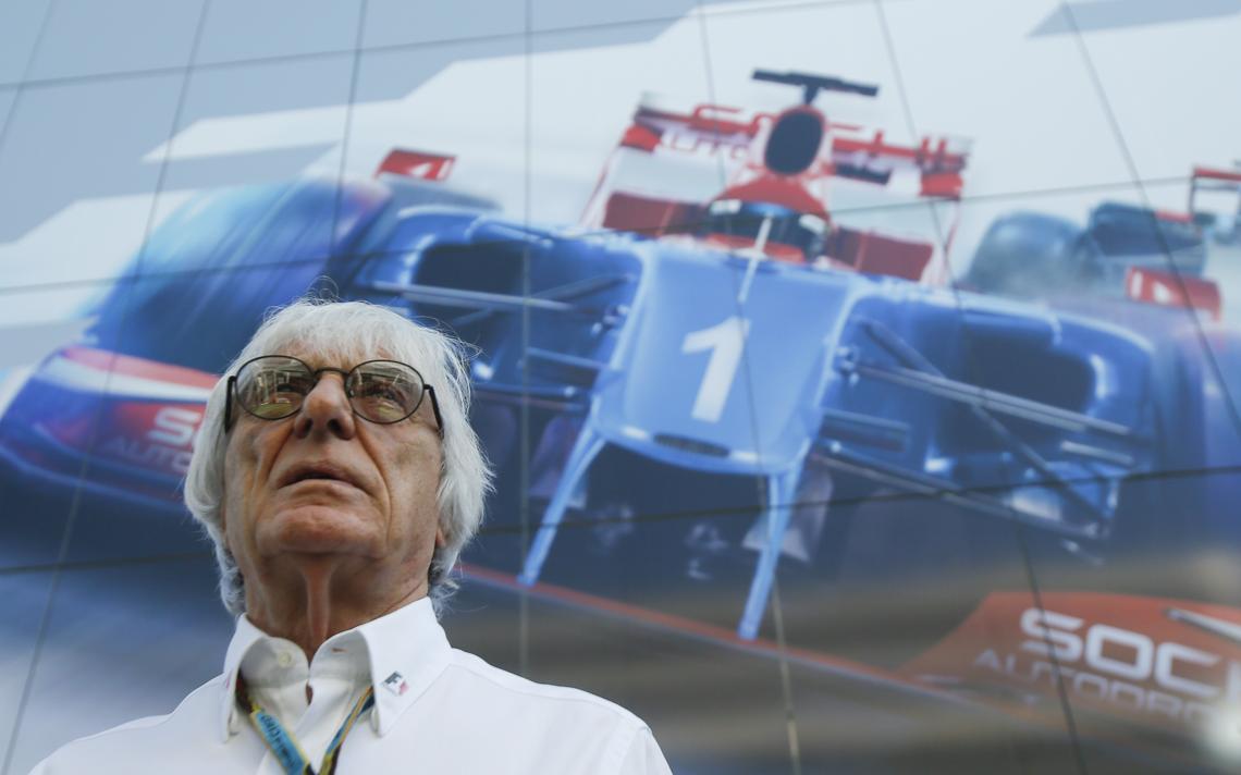 Em primeiro plano, Ecclestone olha para cima. Atrás dele, apenas um painel com a imagem de um carro de Fórmula 1.