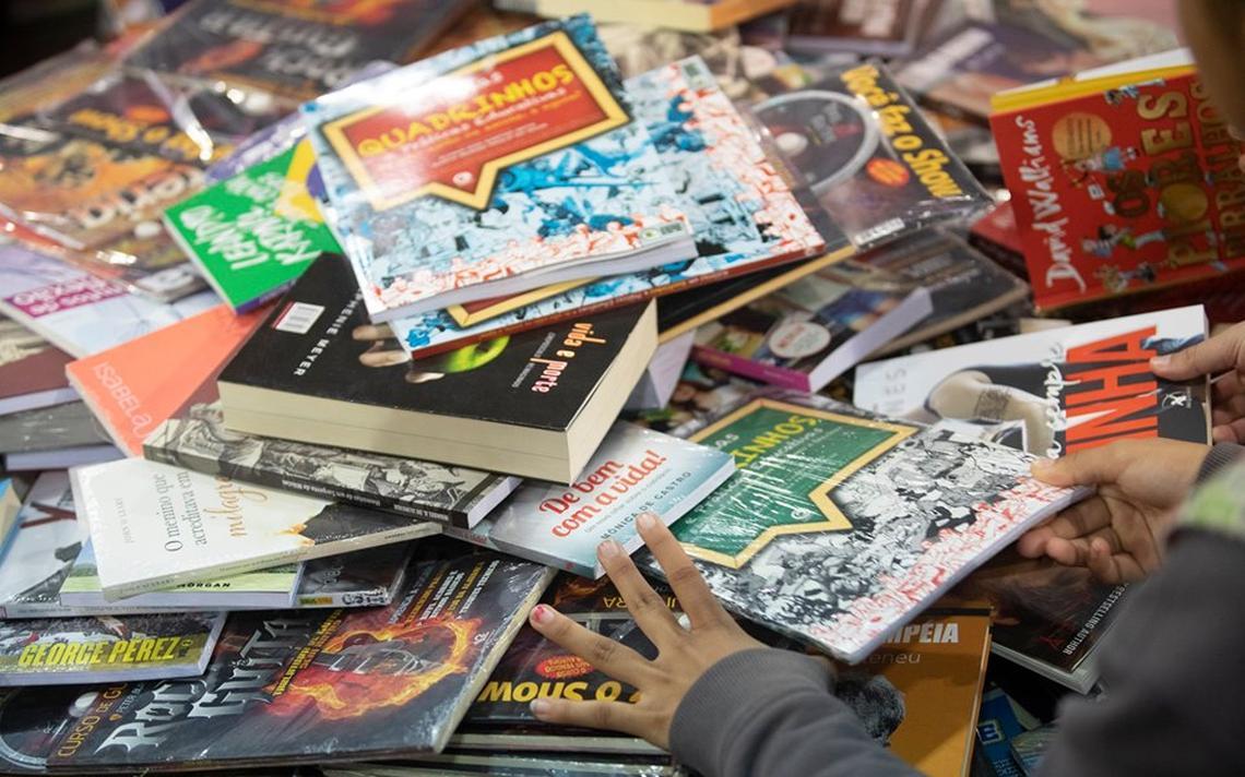 Menina maneja pilha de livros na Bienal do Livro do Rio.