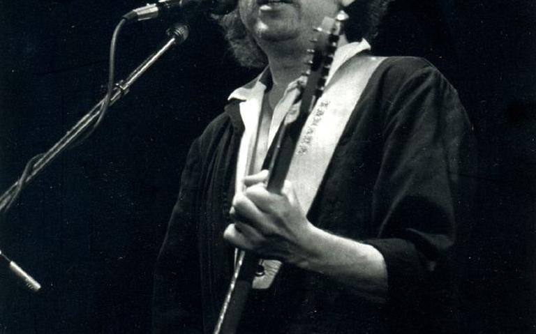 Imagem em preto e branco de Dylan tocando e cantando em show.