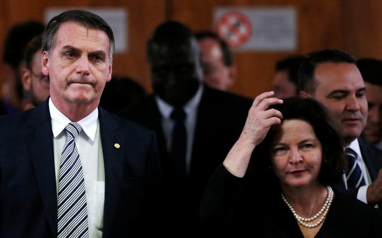 Jair Bolsonaro e Raquel Dodge estão de pé e lado a lado. Atrás deles, outras pessoas em cerimônia. Os dois estão olhando para frente, com semblante sério.