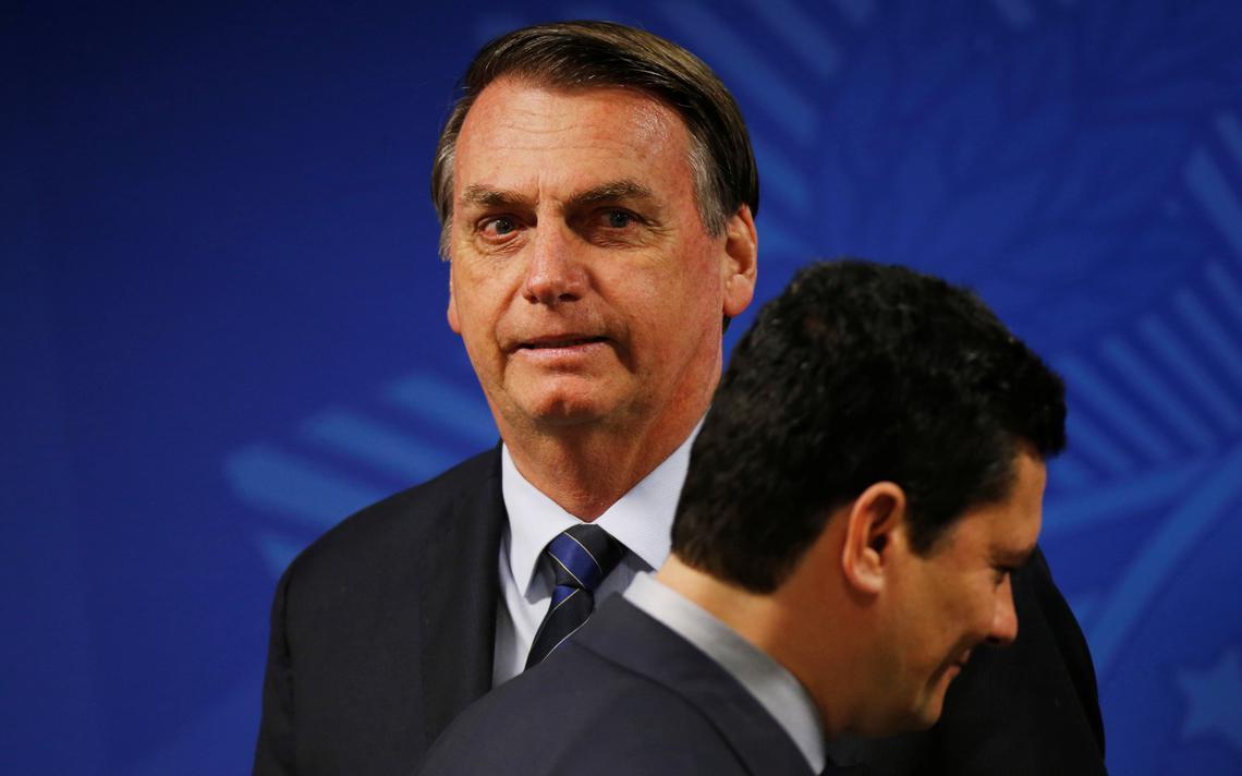 Bolsonaro está de pé e de frente. De perfil, Moro passa à frente de Bolsonaro. Os dois estão sorrindo e olham para direções distintas.