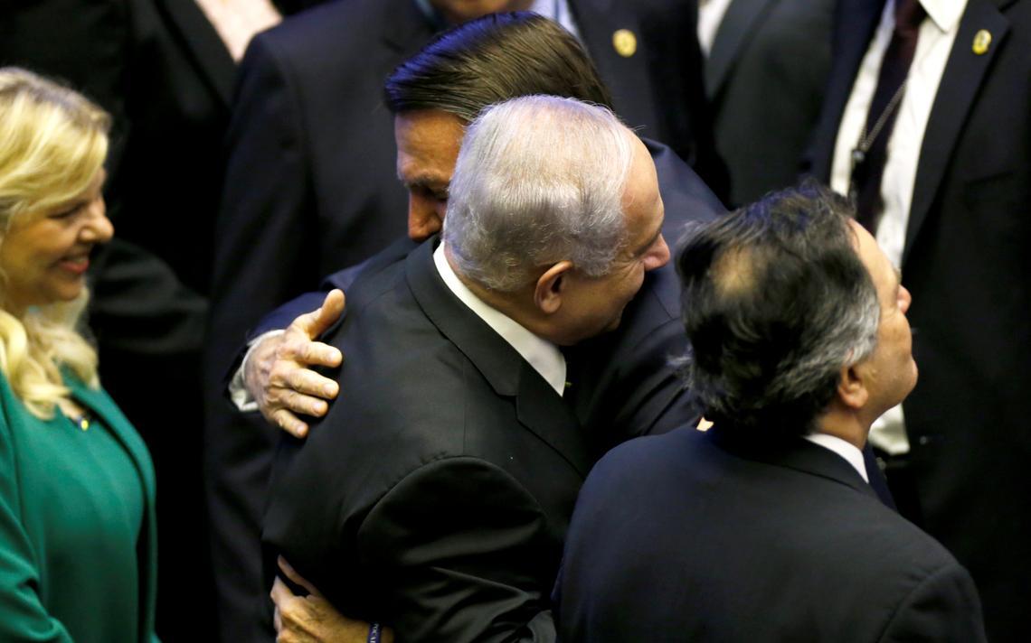 Ao lado de outras autoridades, Bolsonaro e Netanyahu sorriem e se abraçam no plenário do Congresso brasileiro.