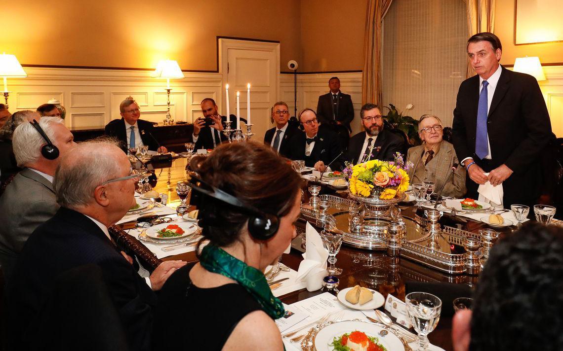 Mesa de jantar formal, com autoridades. Em pé, Bolsonaro discursa e segura um guardanapo de pano com as duas mãos. Ao lado, sentado, está Olavo de Carvalho, que observa Bolsonaro.