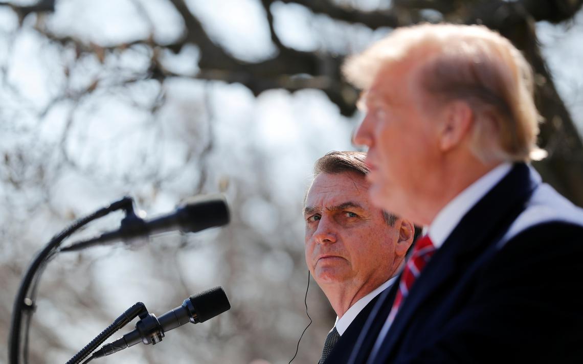 Trump falando ao microfone, em púlpito. Ao lado dele e visto de mais longe, Bolsonaro exibe semblante sério, usa fone de ouvido e observa Trump.