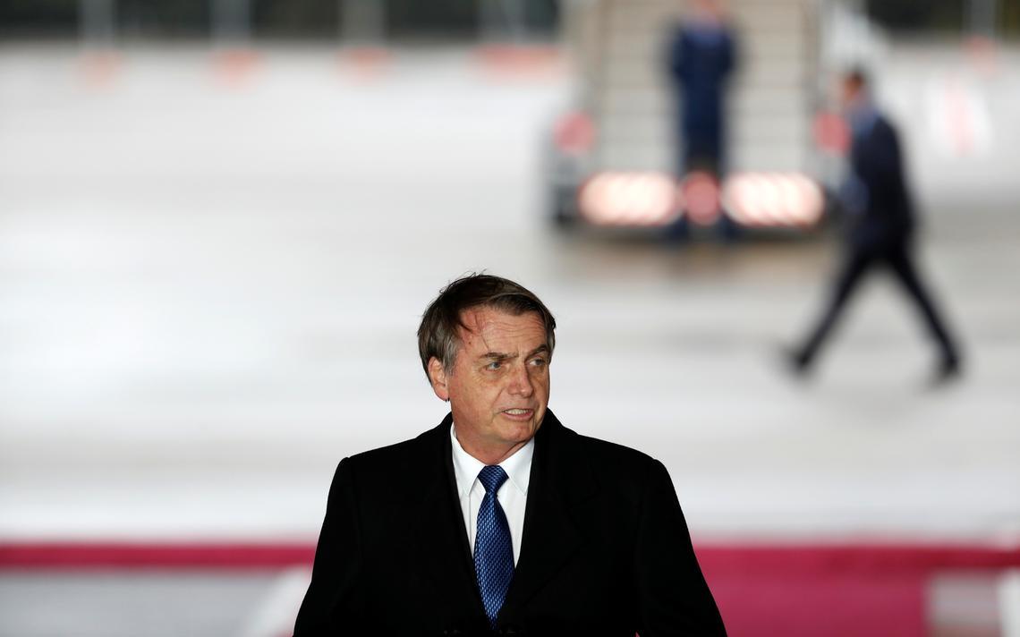 Em pé, Bolsonaro fala em cerimônia. Atrás, tapete vermelho, pista de aeroporto com escada para embarcar em avião e funcionários passando.
