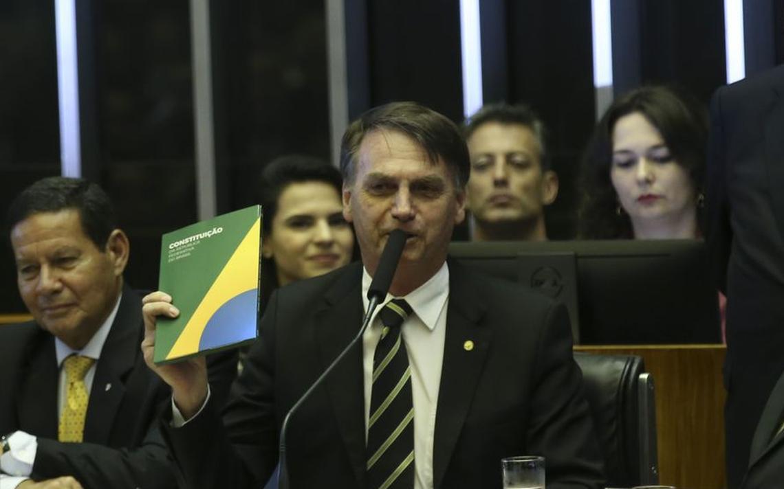 Na mesa da Câmara, Bolsonaro fala ao microfone e exibe um exemplar da Constituição Federal, que ele segura com uma das mãos. Ao lado dele, o vice Mourão e o presidente do Supremo, Dias Toffoli.