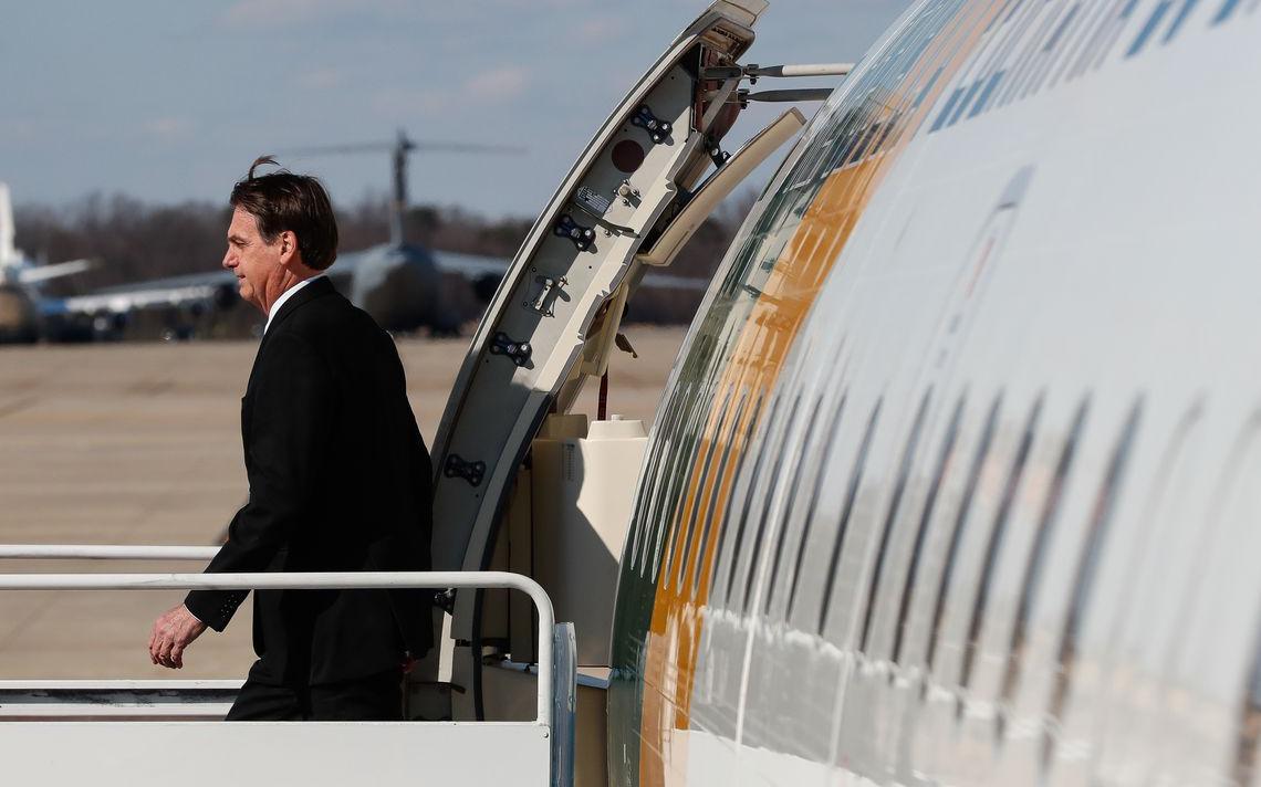 Bolsonaro saindo do avião. Atrás, pista de aviões em base militar.