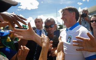O presidente Jair Bolsonaro cumprimenta apoiadores na porta do Palácio do Planalto em manifestação