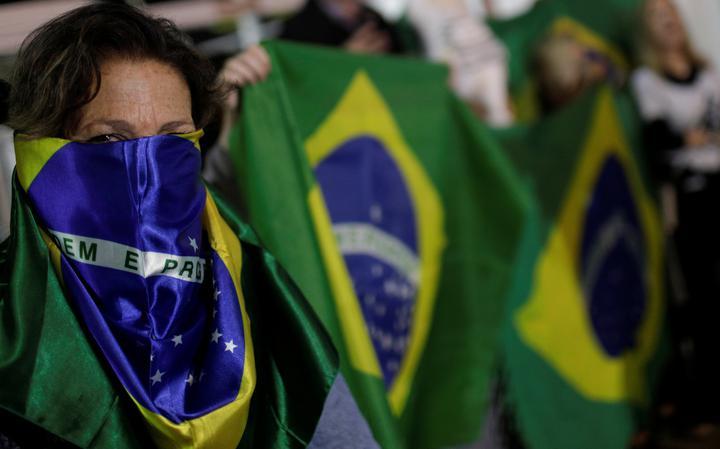 Mulher com o rosto envolto em uma bandeira do Brasil. Atrás, outros manifestantes segurando bandeiras do Brasil.