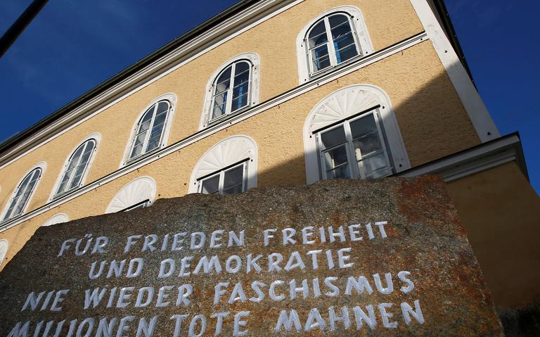 Imóvel em estilo antigo, de três andares. Na frente, uma placa com uma mensagem em alemão.