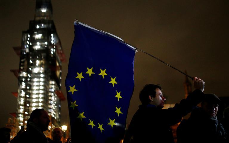 Homem segura bandeira da União Europeia. Outras pessoas ao redor, em frente ao Parlamento.