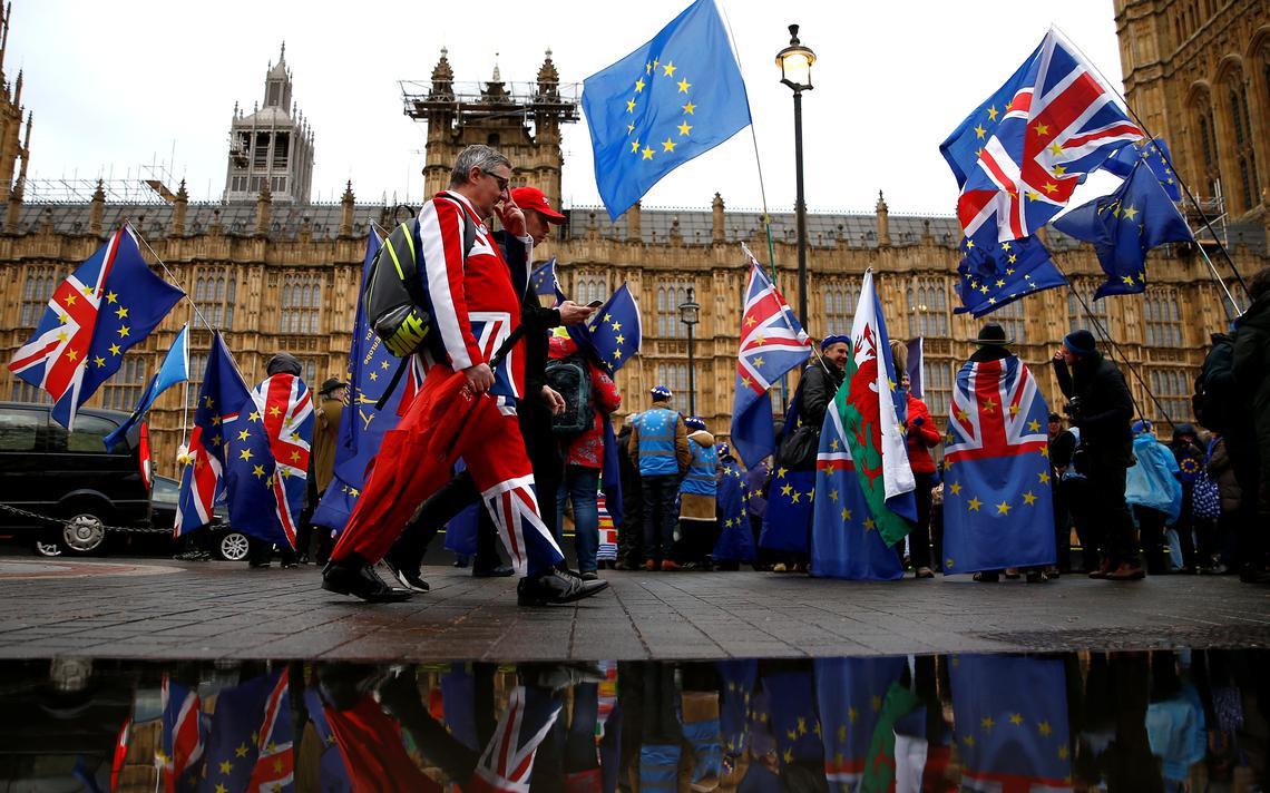 Dezenas de pessoas com roupas, capas e bandeiras do Reino Unido e da União Europeia protestam na rua. Em frente, o prédio do Parlamento.