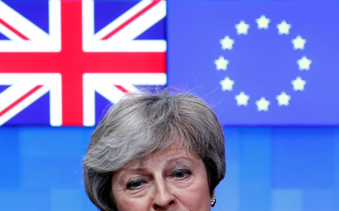 Atrás de May, um painel com a bandeira do Reino Unido e a bandeira da União Europeia lado a lado.
