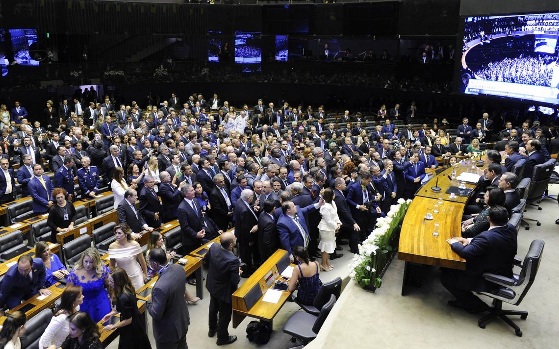 Plenário da Câmara, com parlamentares concentrados em pé ao meio. Todos os da mesa estão ocupados.